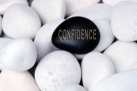 risks ahead: Confidence Concept text on stones, stand out of crowd concept.