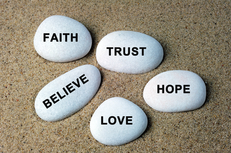Faith, trust, believe, hope and love text on a stones with sand background