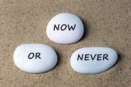 procrastination: Business quotes: now or never text on a stones with sand background Stock Photo