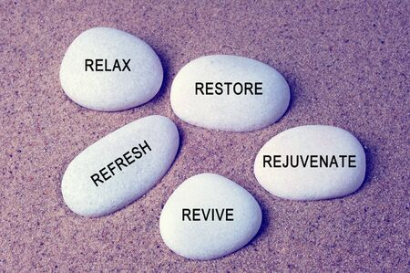 rejuvenate: Wellness, spa and beauty concept - Relax, restore, refresh, rejuvenate and revive text on zen stones retro style background Stock Photo