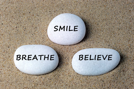 Smile, breathe and believe text on zen stone. Reklamní fotografie