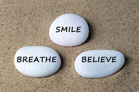 exhilarated: Smile, breathe and believe text on zen stone. Stock Photo