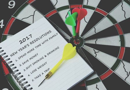 bull's eye: 2017 new years resolutions on notepad with darts on bulls eye, retro style