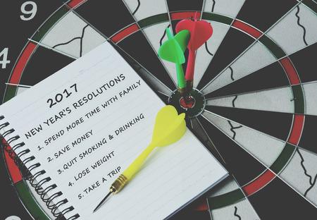 bulls eye: 2017 new years resolutions on notepad with darts on bulls eye, retro style