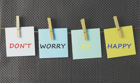 dont worry: Life inspiration quotes dont worry, be happy on colorful paper attached on a string with clothes pin Stock Photo