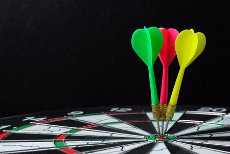Three darts on bulls eye with black background horizontal shot