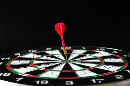 Red darts on bullseye target.