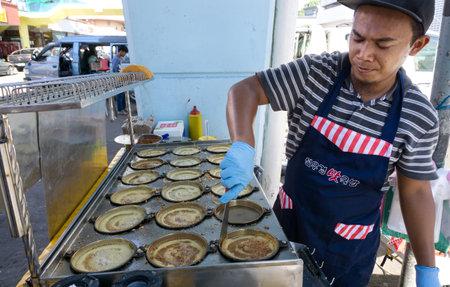 Kota Kinabalu, Malaysia - August 01, 2017: Man cooking a Malaysian sweet food known as Apam Balik or pancake at segama area in Kota Kinabalu city, Sabah Borneo. Sajtókép