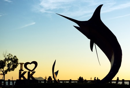 pez vela: Kota Kinabalu, Malaysia - August 01, 2017: Silhouette of the famous Marlin fish statue at Sabah capital. The statue was inaugurated on 2nd February 2000 when Kota Kinabalu achieved city status.