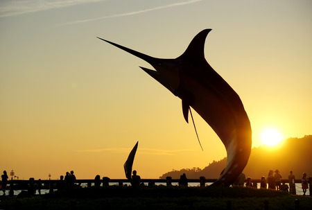Kota Kinabalu, Malaysia - August 01, 2017: Silhouette of the famous Marlin fish statue at Sabah capital. The statue was inaugurated on 2nd February 2000 when Kota Kinabalu achieved city status.
