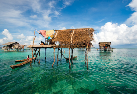 Semporna, Malaysia - 19 April, 2015: A Bajau laut floating village of stilted houses off the coast of Borneo in The Celebes Sea in the vicinity of Sipidan and Tun Sakaran Marine Park.