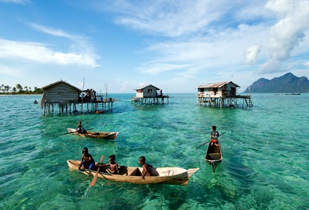 Semporna, Malaysia - 18 April, 2015: Young Bajau laut boy paddling a boat near stilted houses off the coast of Borneo in The Celebes Sea in the vicinity of Sipidan and Tun Sakaran Marine Park.