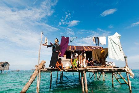 センポルナ, マレーシア: 2011 年 9 月 17 日: 酒樽サカラン海洋公園で大げさな村で家バルコニーのバジャウ ラウトの家族。