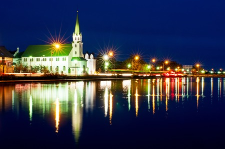 Night view of the Free Church in Reykjav�k, Frikirkjan i Iceland over the Tjornin lake in Iceland. Stock Photo
