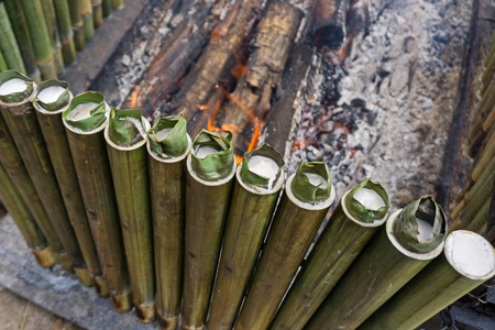 Cooking lemang, a type of bamboo rice. Lemang is made of glutinous rice that is cooked with coconut milk in hollowed bamboos. It is commonly found in Brunei, Indonesia, Malaysia and Singapore.