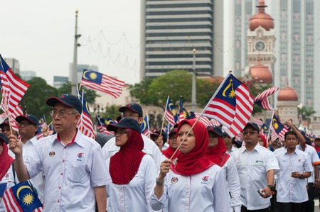 Kuala Lumpur, Malaysia - August 31, 2014: Parade participants waving a Malaysian flags during Malaysias 57th Independence day parade held in Merdeka Square, Kuala Lumpur.