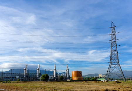 Power plant, energy power station and electric pylon, high-voltage electric tower against blue sky Archivio Fotografico