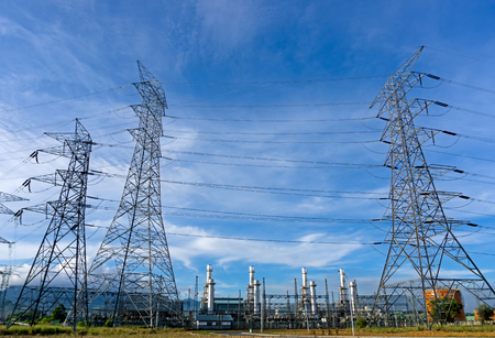 Power plant, energy power station and electric pylon, high-voltage electric tower against blue sky.