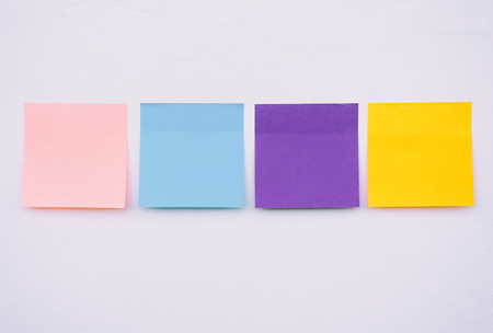 Colorful sticky paper on a wall, pastel colors. Foto de archivo