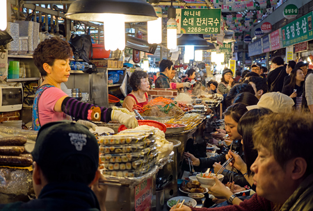 Seoul, South Korea - April 08, 2017: Woman vendor serving customers at Gwangjang Market in Seoul. It's one of the ultimate places to experience traditional Korean street food and culture all one roof.