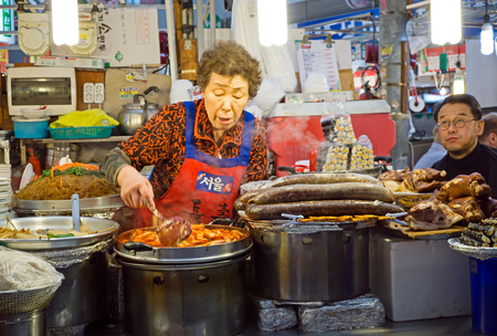 Seoul, South Korea - April 08, 2017: Woman vendor preparing a food at Gwangjang Market in Seoul. It's one of the ultimate places to experience traditional Korean street food and culture all one roof. Editorial