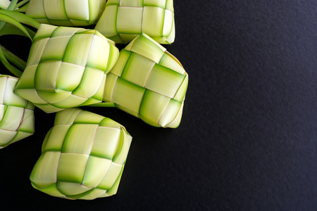 Rice dumpling casing or also know as ketupat made from coconut palm leaf on black background. Ketupat is a type of dumpling made from rice packed inside a woven palm leaf pouch.