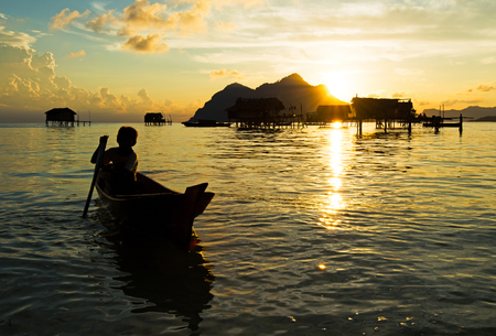 Silhouette of bajau laut young boy paddling a boat during sunrise at the shore of Maiga Island in the vicinity of Sipidan Island and Tun Sakaran Marine Park, Semporna, Sabah Borneo, Malaysia. Editorial