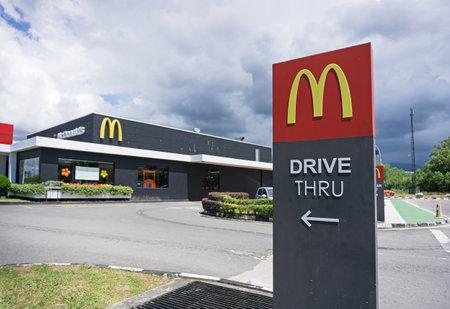Kota Kinabalu, Malaysia - October 05, 2017: McDonalds logo drive thru direction arrow. McDonald's Corporation is the world's largest chain of hamburger fast food restaurants.