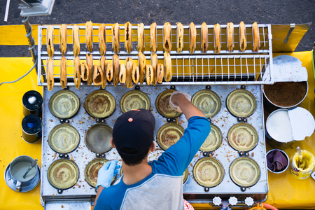 Top view of man cooking a Malaysian sweet food known as Apam Balik or pancake at segama area in Kota Kinabalu city, Sabah Borneo.