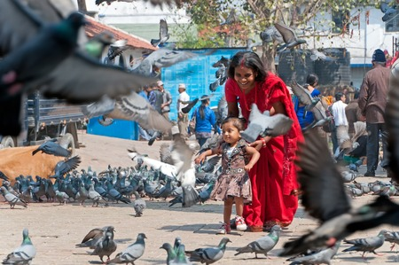 Kathmandu, Nepal - March 19, 2013: Woman in red sari with her daughter feeding a flock of pigeons at Patan Durbar square in Kathmandu Valley.
