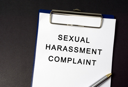 Sexual harassment complaint word on paper, black background