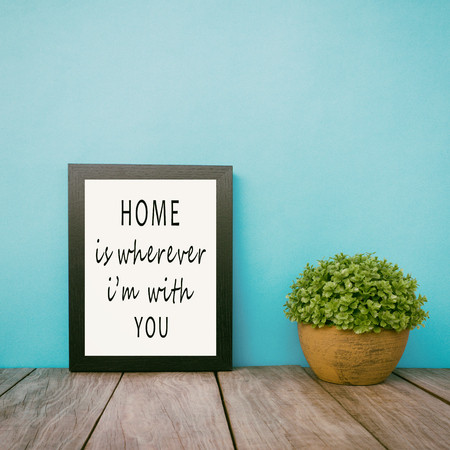 Motivational and inspirational life quotes - Home is wherever i'm with you. Frame and plant with teal blue background, retro style.