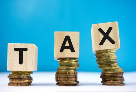 Tax word on top of coins stack Stock Photo