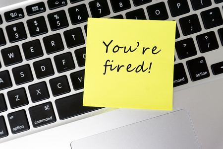Youre Fired word on sticky note on top of laptop Stock Photo