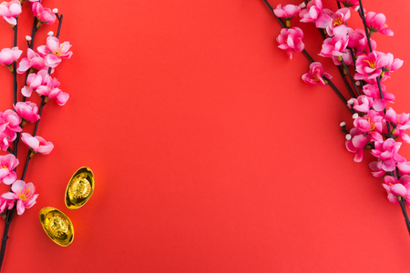 Chinese New Year Background Ornaments, Plum Flowers and Gold Ingots with Chinese Word Happiness and Prosperity. Red background.