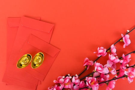 Chinese New Year Background Ornaments, Red Envelopes, Plum Flowers and Gold Ingots with Chinese Character Happiness and Prosperity. Red background.