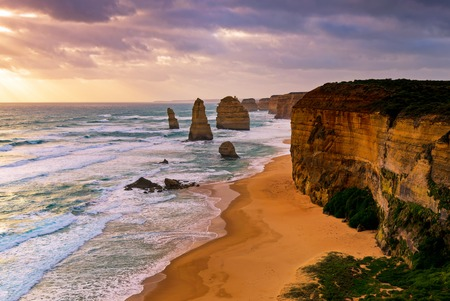 Sunset over Twelves Apostles in Great Ocean Road, Victoria, Australia. The Twelve Apostles is a collection of limestone stacks off the shore of the Port Campbell National Park. Stock Photo