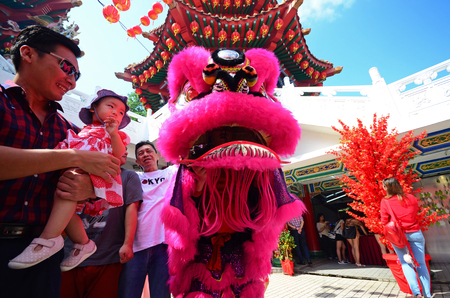 Kuala Lumpur, Malaysia - February 16, 2018: Man and child at lion dance during Chinese New Year celebration in Thean Hou Temple.