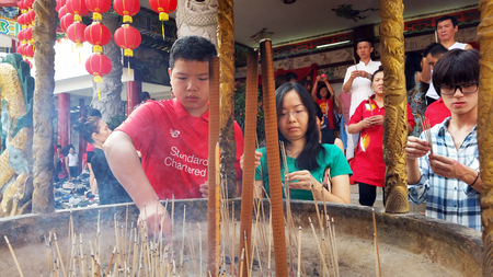 Kuala Lumpur, Malaysia - February 16, 2018: People burn incense sticks and pray for good fortune during Chinese New Year Day in Thean Hou Temple.