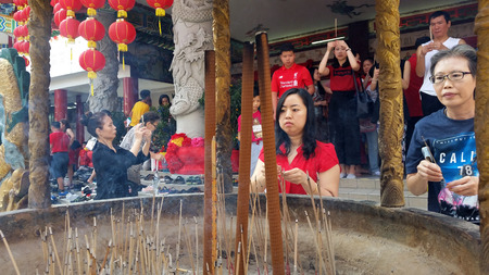 Kuala Lumpur, Malaysia - February 16, 2018: Women burn incense sticks and pray for good fortune during Chinese New Year Day in Thean Hou Temple. Editorial