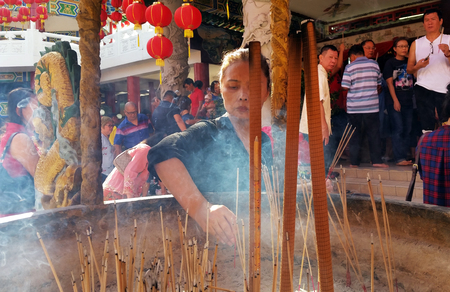 Kuala Lumpur, Malaysia - February 16, 2018: Woman burn incense sticks and pray for good fortune during Chinese New Year Day in Thean Hou Temple. Editorial