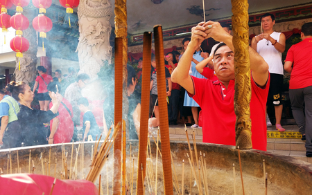 Kuala Lumpur, Malaysia - February 16, 2018: Man burn incense sticks and pray for good fortune during Chinese New Year Day in Thean Hou Temple.