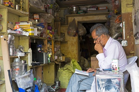 Mandawa, India - February 24, 2018: Unidentified Indian man reading a book inside his store.