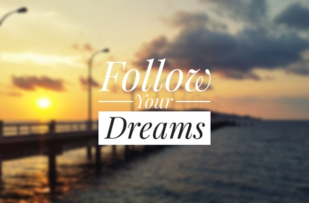 Inspirational quote - Follow your dreams. Blurry sunset background. Stock Photo