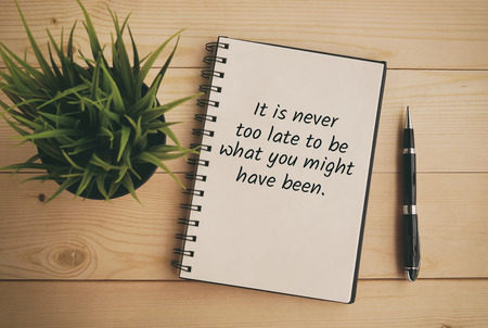 Inspirational and motivation life quote on note pad - It is never too late to be what you might have been. Retro style. 写真素材