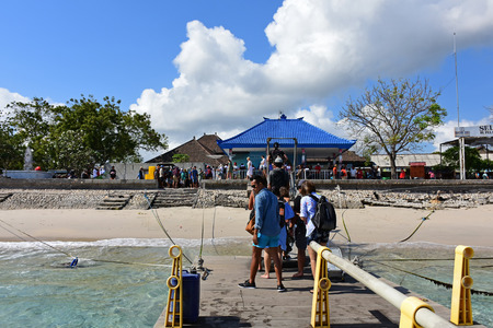 Nusa Penida, Indonesia - September 16, 2018: Tourists and locals at the jetty in Nusa Penida island, one of most famous travel destinations in Bali.