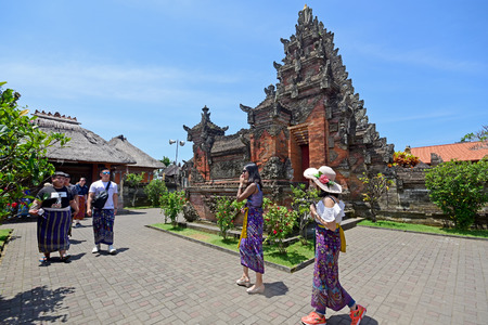 Bali, Indonesia - September 15, 2018: Tourists at Puseh temple, located at Batuan village. It is a Balinese temple with interesting stone carvings & sculptures, sarongs required for entrance.