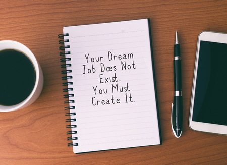 Life Inspirational And Motivational Quotes - Your Dream Job Does Not Exist. You Must Create It. Notepad With Coffee, Pen and Smart Phone.