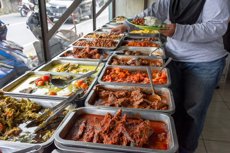Indonesian food buffet dishes consist of meat, chicken, seafood and vegetables at Javanese restaurant in Bali.