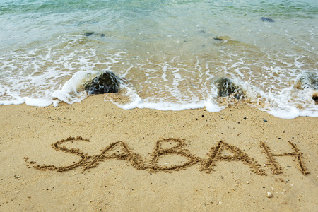 Sabah word on a sand beach with waves - travel concept, Malaysia. 写真素材
